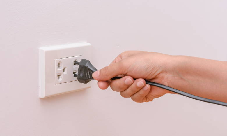 hand putting plug into electrical socket