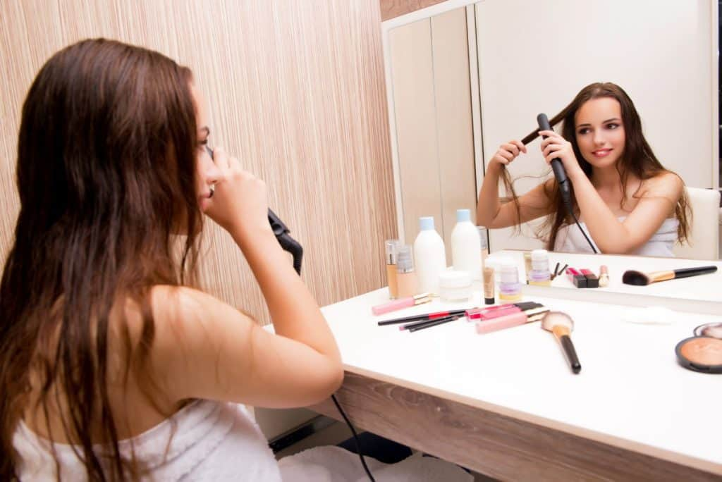 woman straightening hair with mirror
