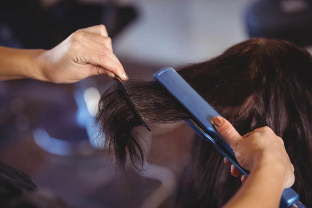straightening hair with blue flat iron
