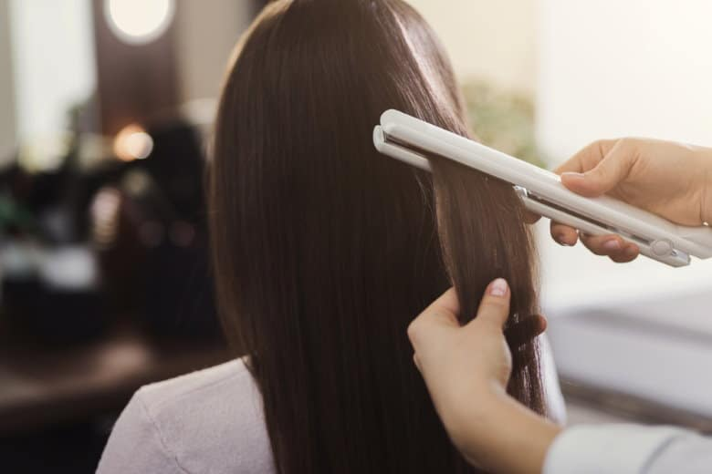 hairdresser using titanium flat iron