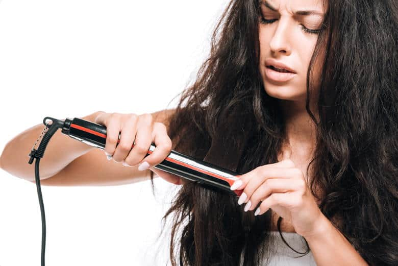 woman trying to straighten hair without protectant