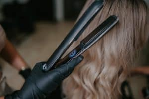 gloved hand holding ghd flat iron