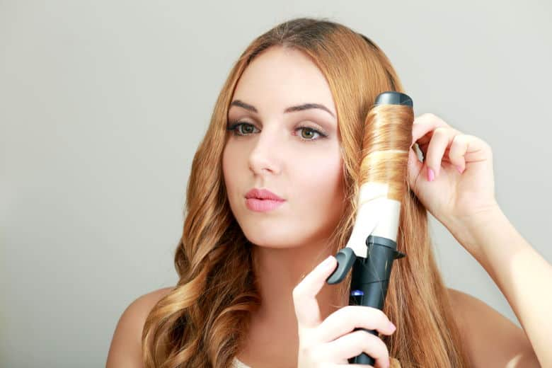 woman curling hair with large barrel curling iron